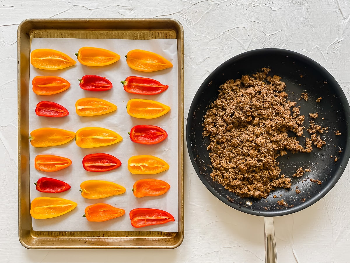 Bell pepper shells on a baking sheet with a skillet of nacho filling on the side.