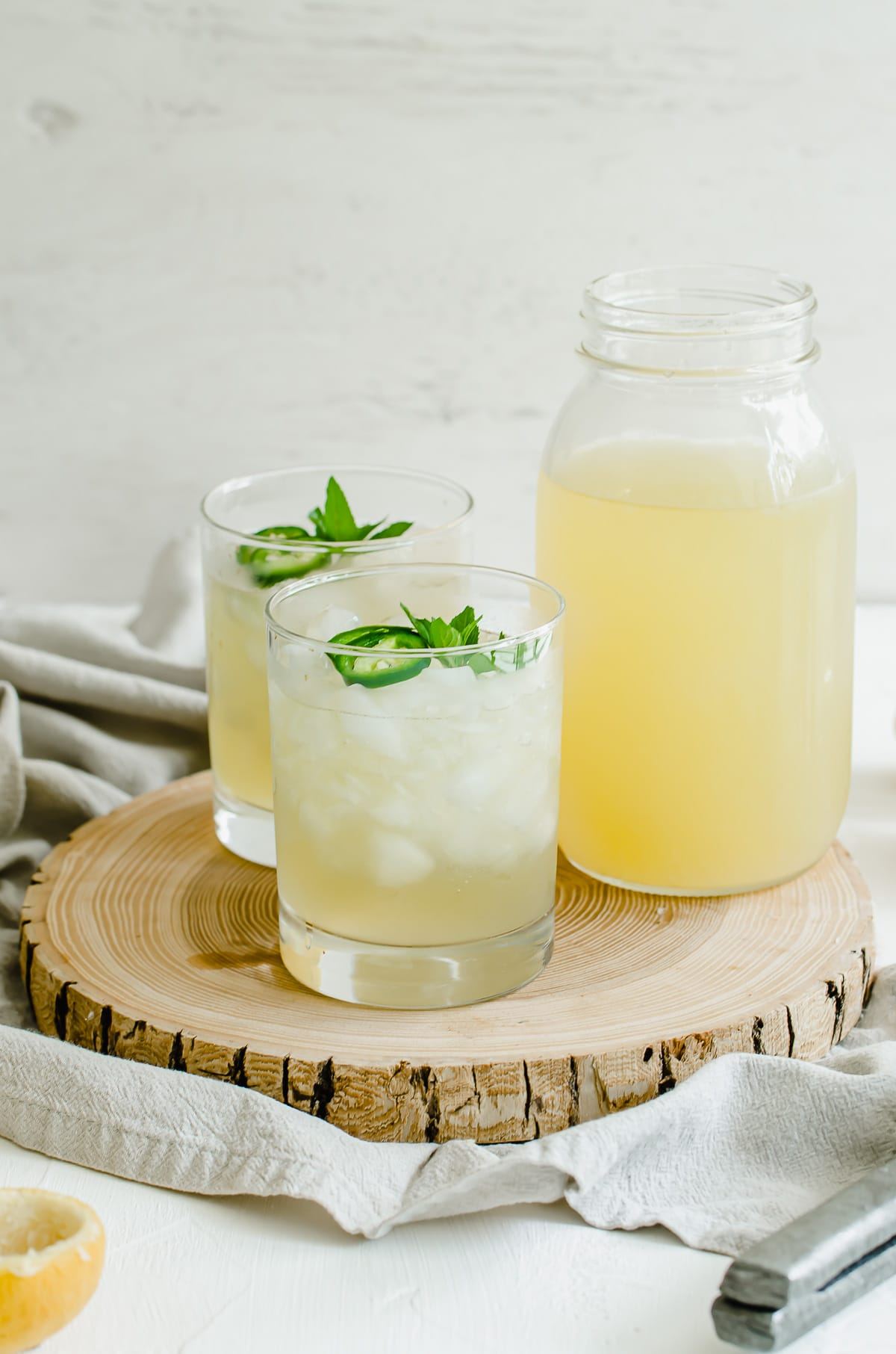 A straight-on shot of a wooden serving tray with freshly squeezed lemonade.