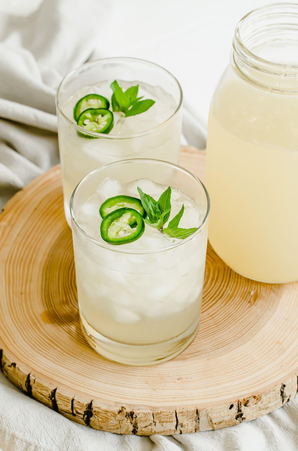 Glasses of lemonade with a large Mason jar of lemonade on the side.