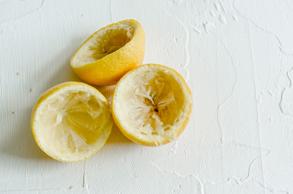 Three lemon halves with the pulp and juice removed on a white surface.