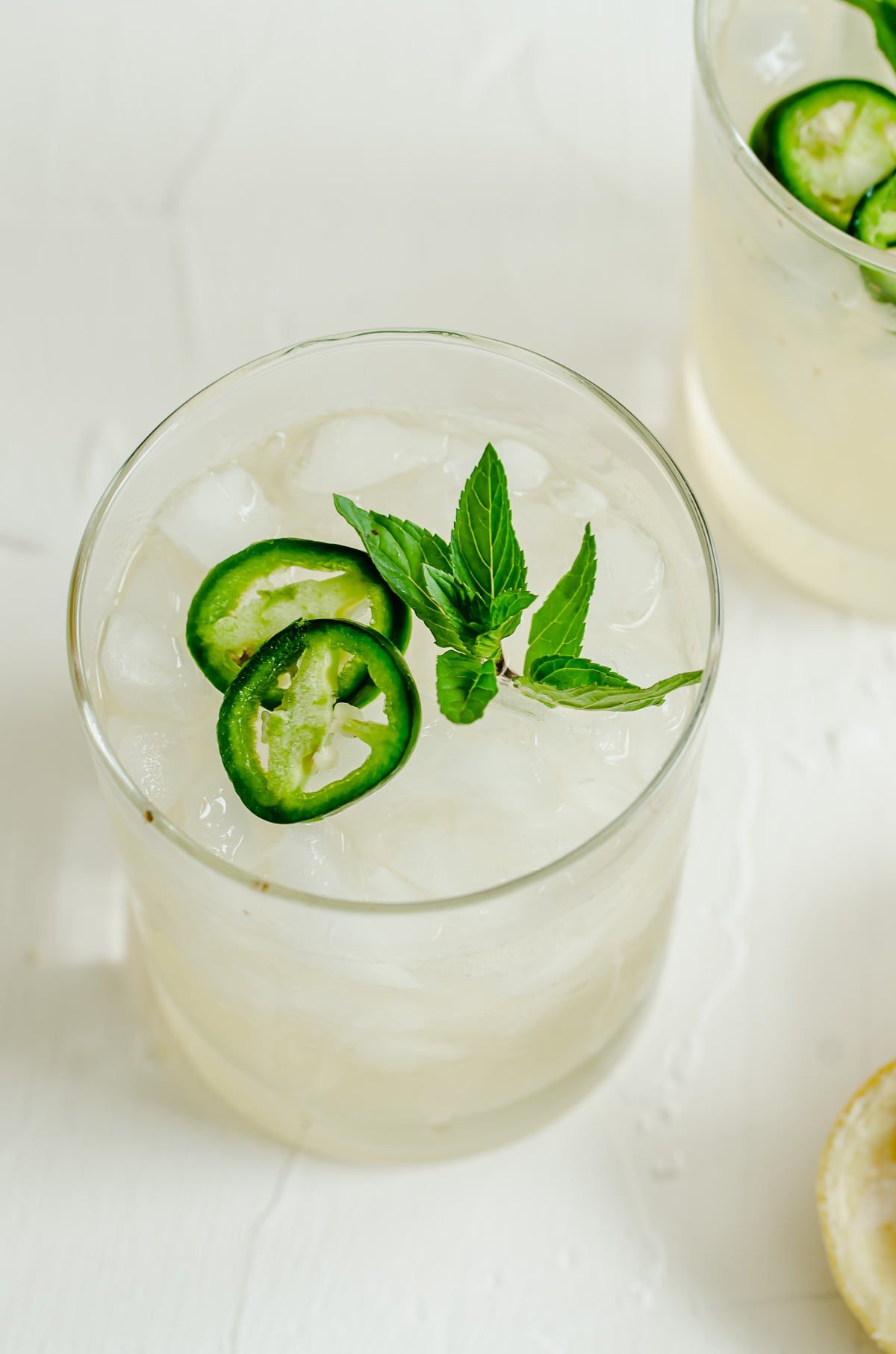 A glass of a lemon beverage garnished with jalapeño slices and a mint sprig.