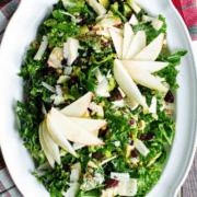 Overhead shot of a kale salad on a scalloped-edge white platter.