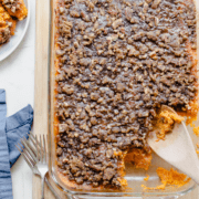 A large dish of sweet potato casserole with a spoon taking a serving out of the side.
