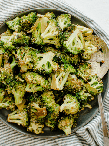 A square image with a gray plate of roasted broccoli.