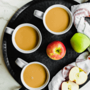 A black tray with three mugs of caramel apple cider and apples on the side.