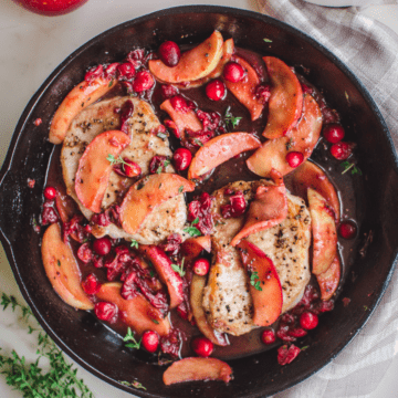 Pan-fried pork chops in a cast-iron skillet with a cranberry apple pan sauce.