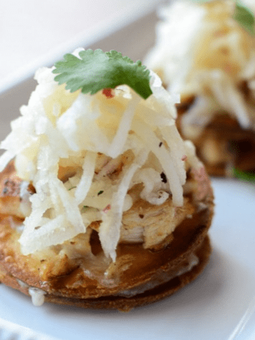 A side shot of a mini chicken tostada topped with apple slaw and a cilantro leaf.