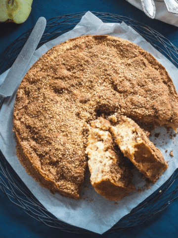 A cinnamon apple cake with two slices cut out on a piece of parchment paper with a navy blue background.