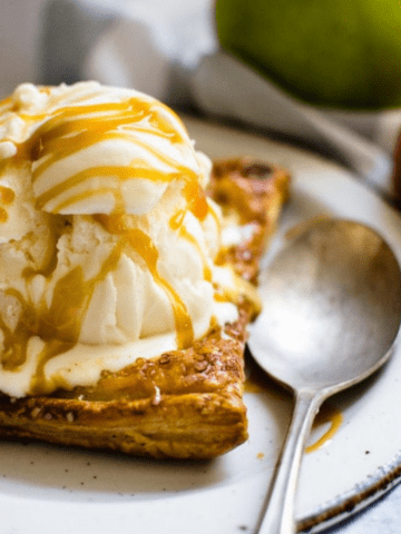 A side shot of an apple tart on a white plate topped with ice cream and caramel sauce.