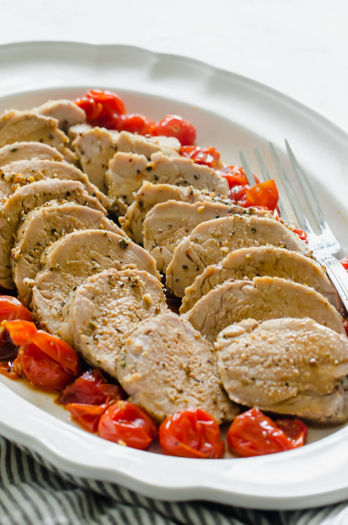 A close up shot of sliced pork with roasted tomatoes.