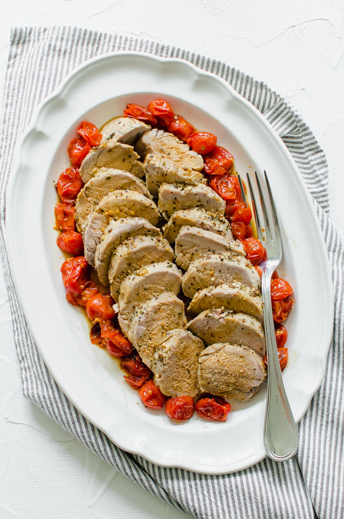 Slices of Tuscan roasted pork surrounded by roasted tomatoes on a white platter.