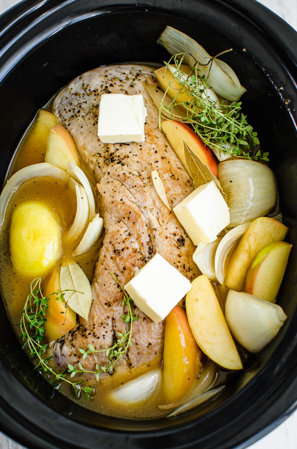 A pork loin roast in a slow cooker with apples, onions, thyme, butter pats, and apple cider.