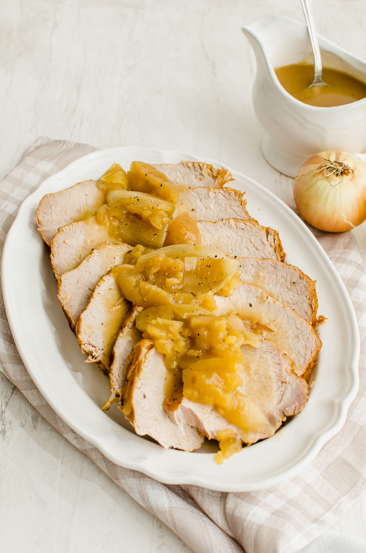 Slices of pork loin with apples and onions on a white platter with a gravy boat on the side.