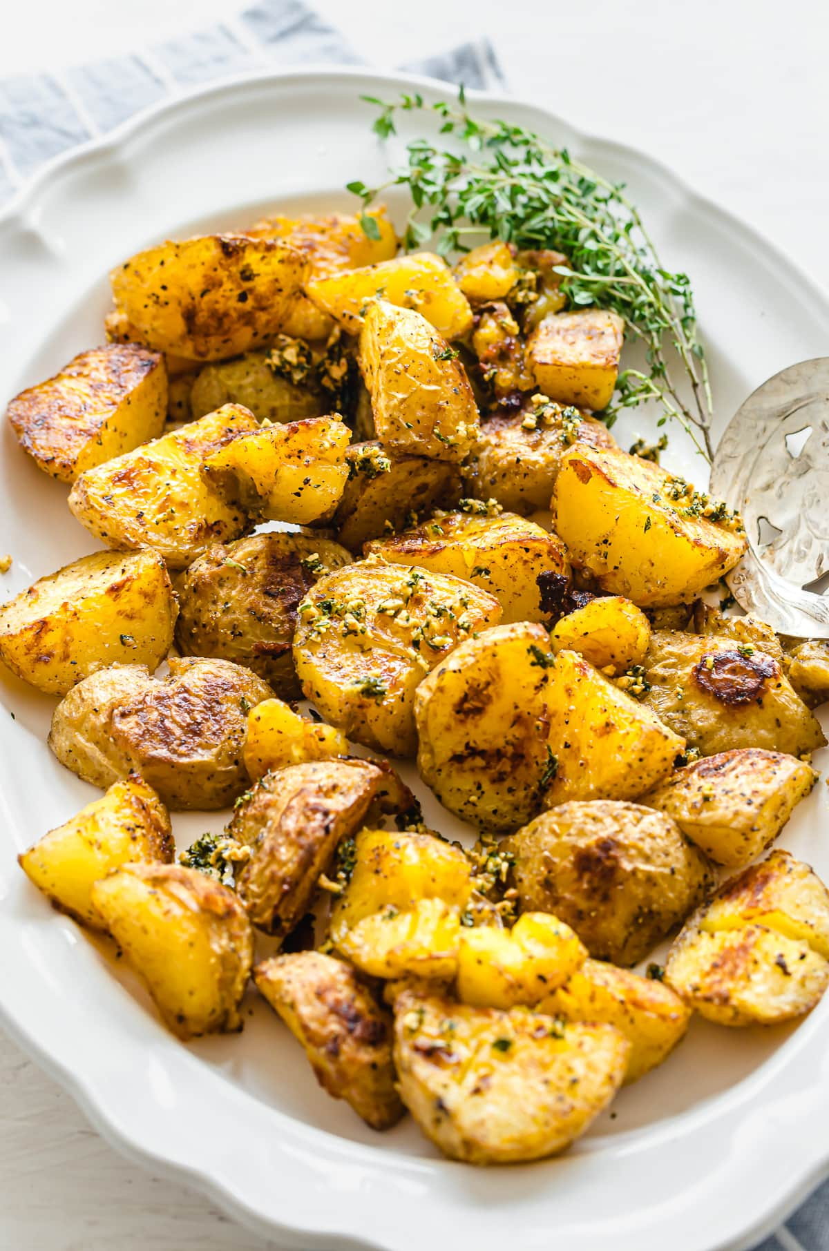 A close-up shot of roasted potatoes on a white serving platter.