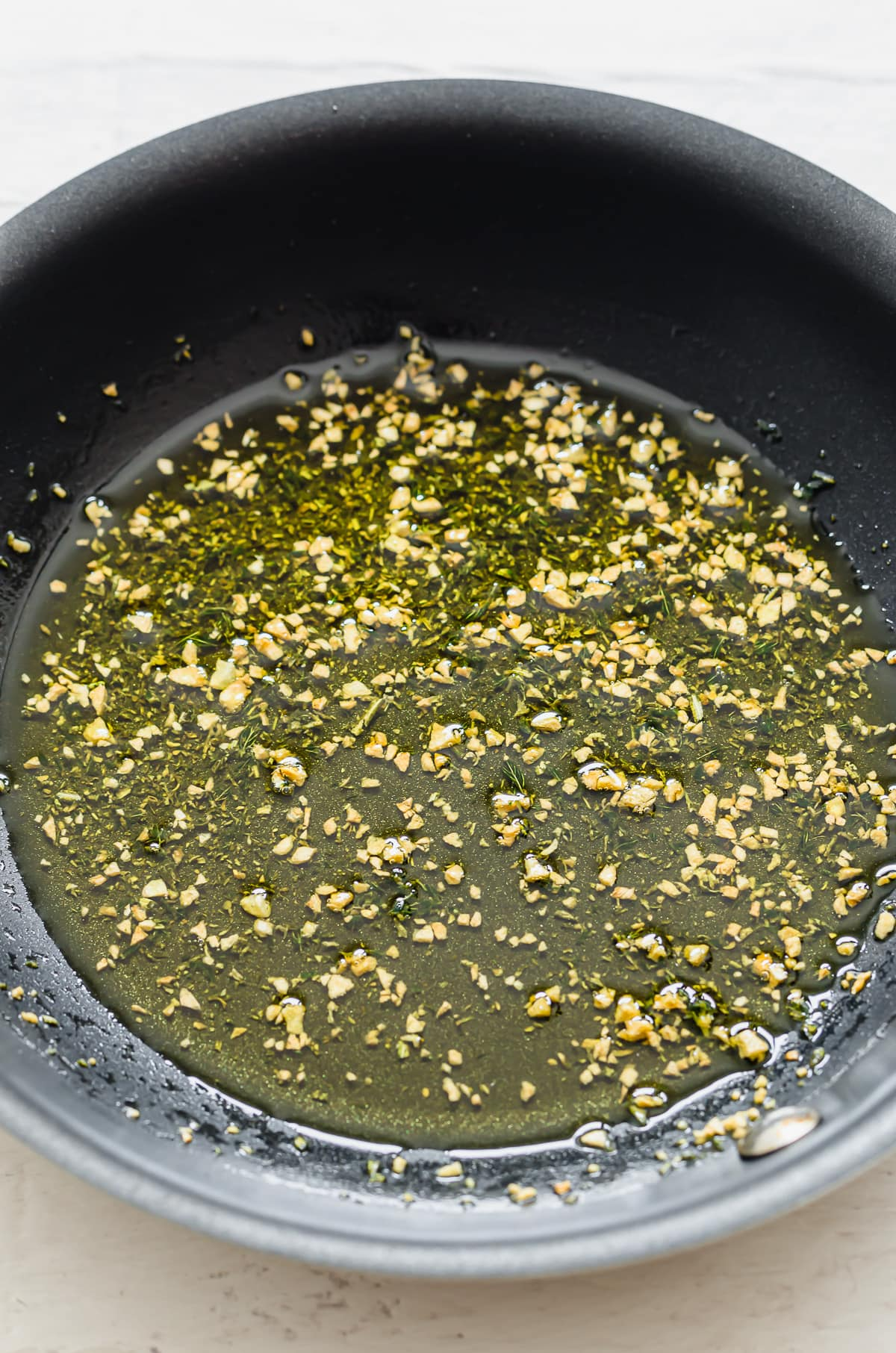 A skillet with olive oil, chopped garlic, and herbs.
