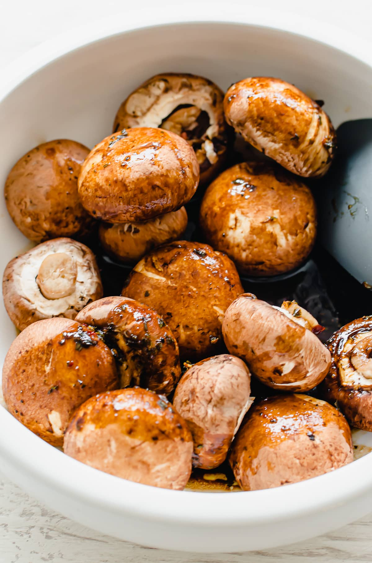 A white bowl with bella mushrooms being tossed in a balsamic sauce.
