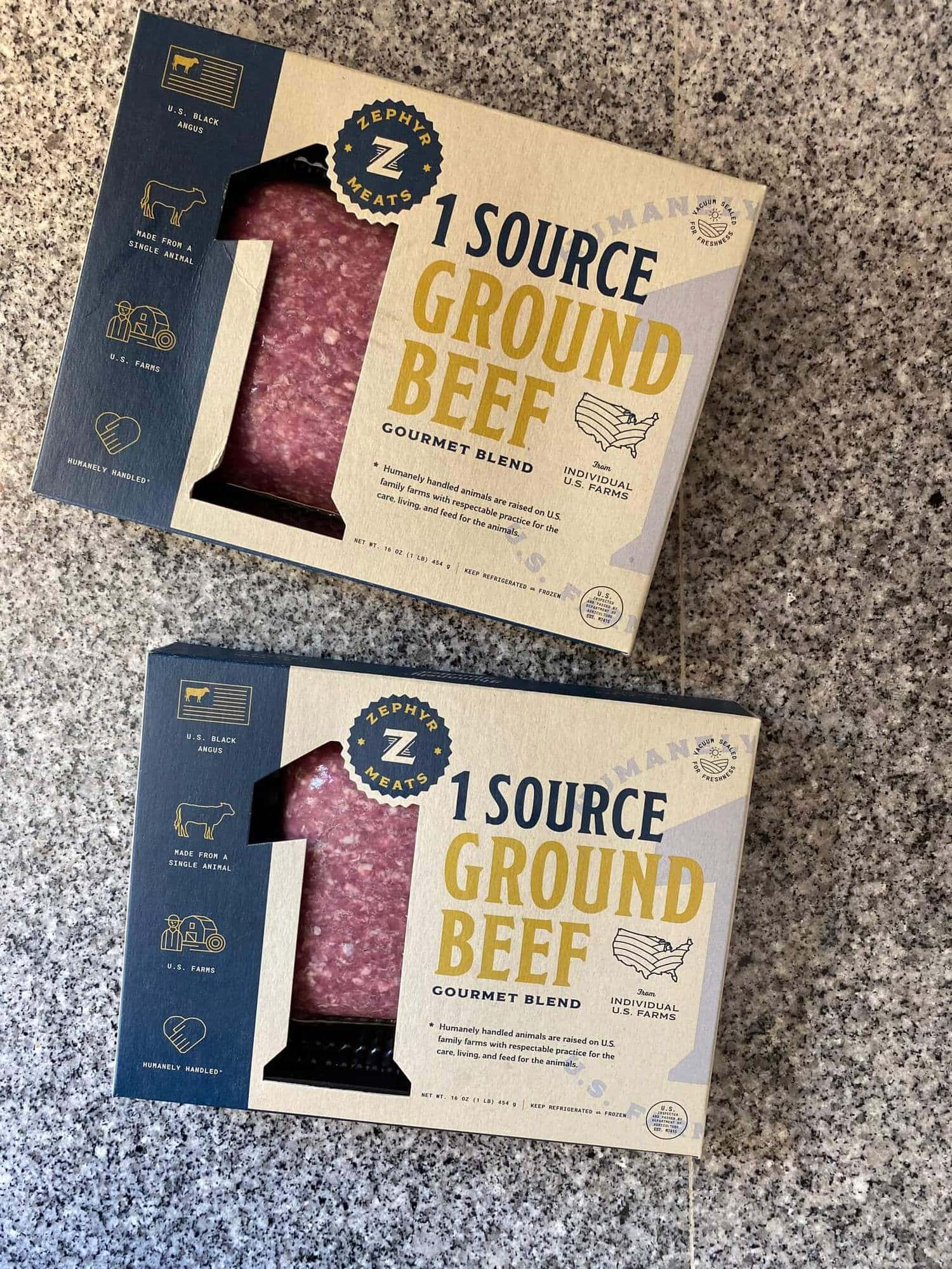 Two packages of 1 Source Ground Beef on a blue granite countertop.