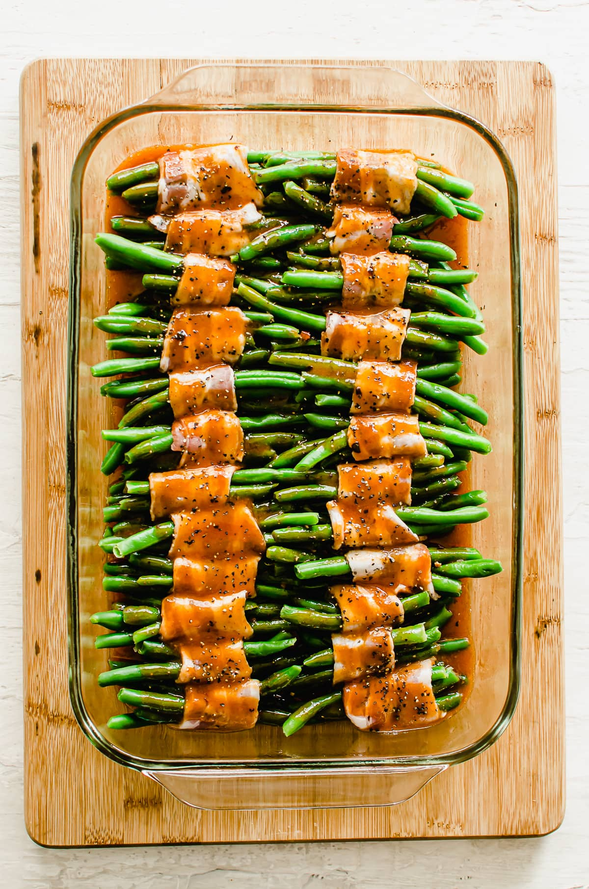 Unbaked bacon-wrapped green beans with catalina dressing in a dish.