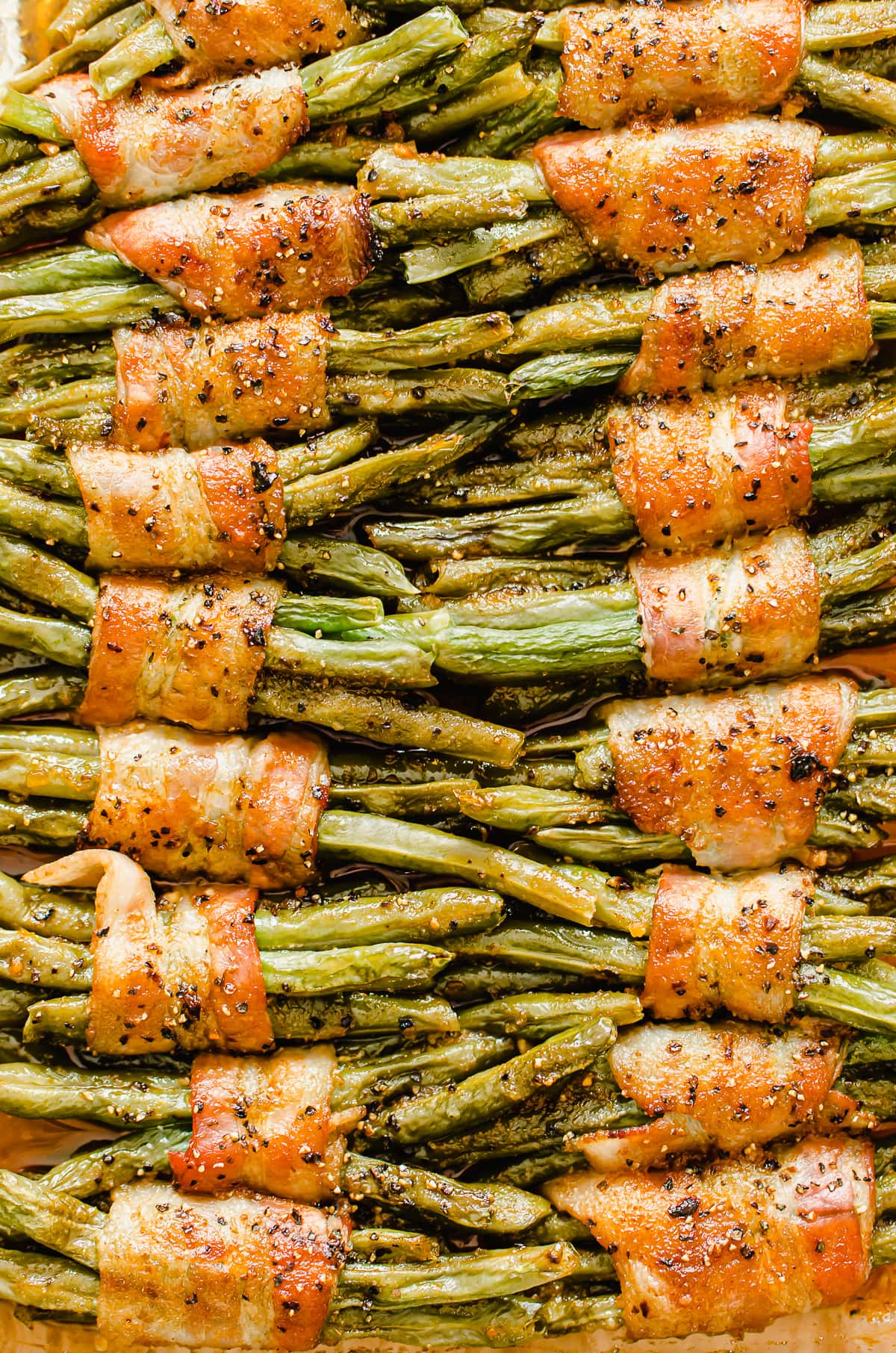 A close-up shot of green bean bundles in a baking dish to show texture once they are baked.