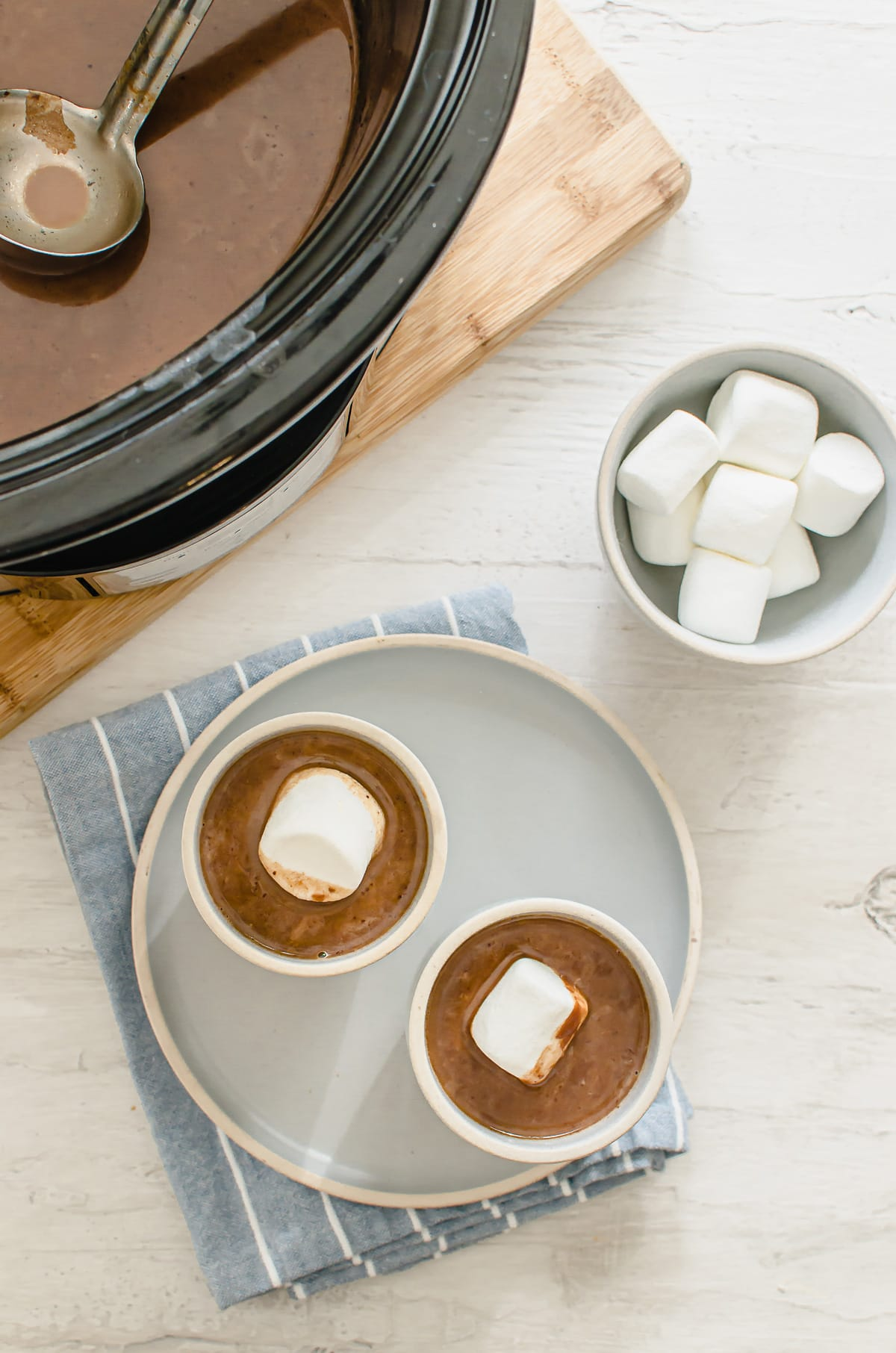 A slow cooker with hot chocolate next to two cups of chocolate with a bowl of marshmallows on the side.