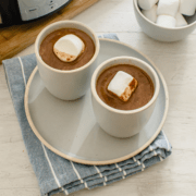 Two cups of hot chocolate topped with jumbo marshmallows.