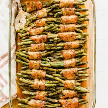 An overhead shot of a glass baking dish with green bean bundles and a serving spoon.