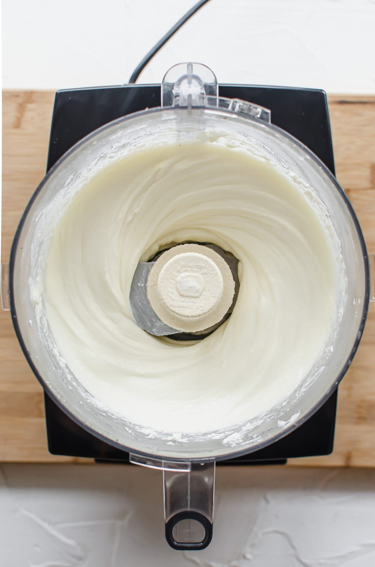 Mixed cheesecake batter in the bowl of a food processor.