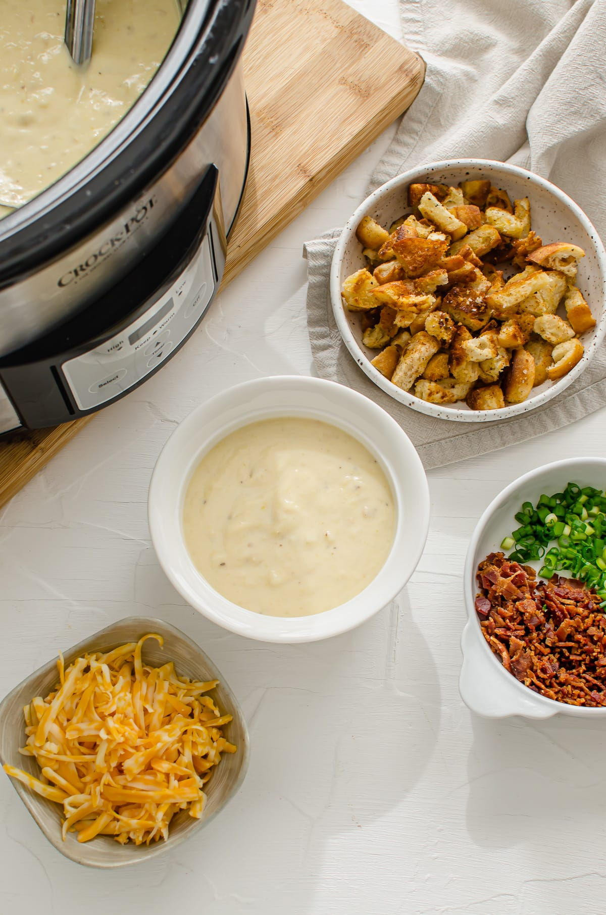 A bowl of potato soup next to the slow cooker with bowls of toppings on the side.