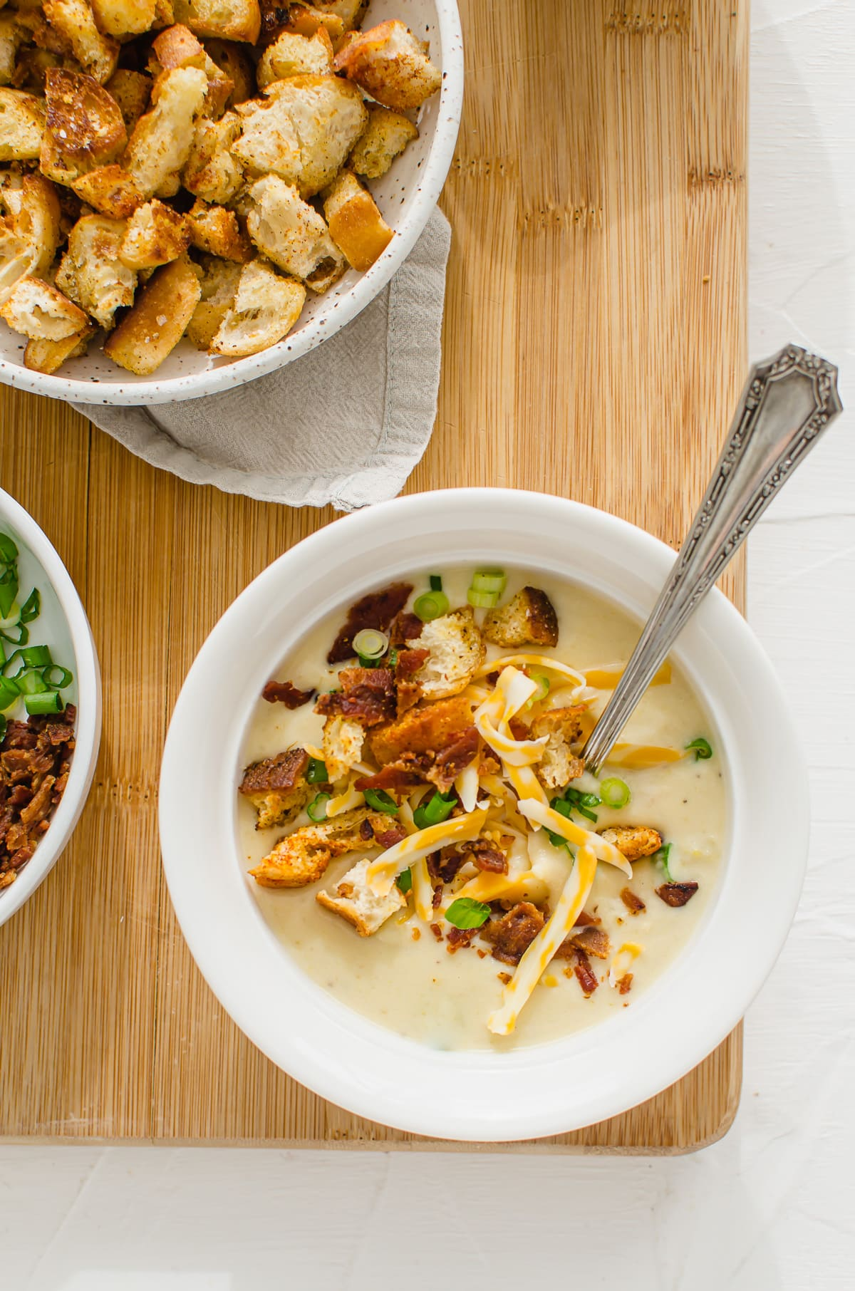 An overhead shot of potato leek soup in a white bowl with a bowl of croutons on the side.