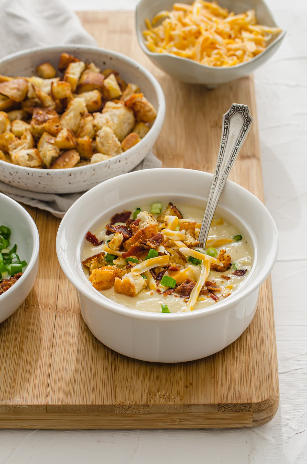 A white bowl of potato leek soup topped with croutons, bacon, cheese, and scallions.