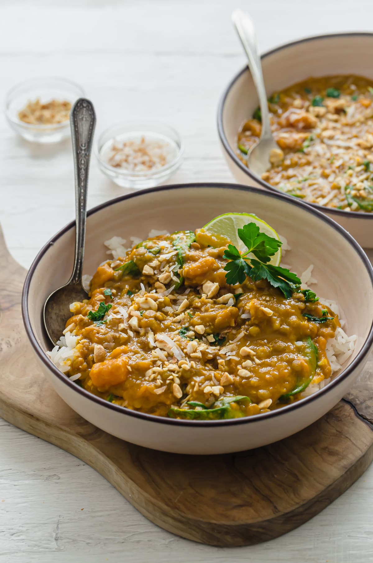 Two bowls of sweet potato lentil curry with small bowls of toasted coconut and chopped peanuts on the side.
